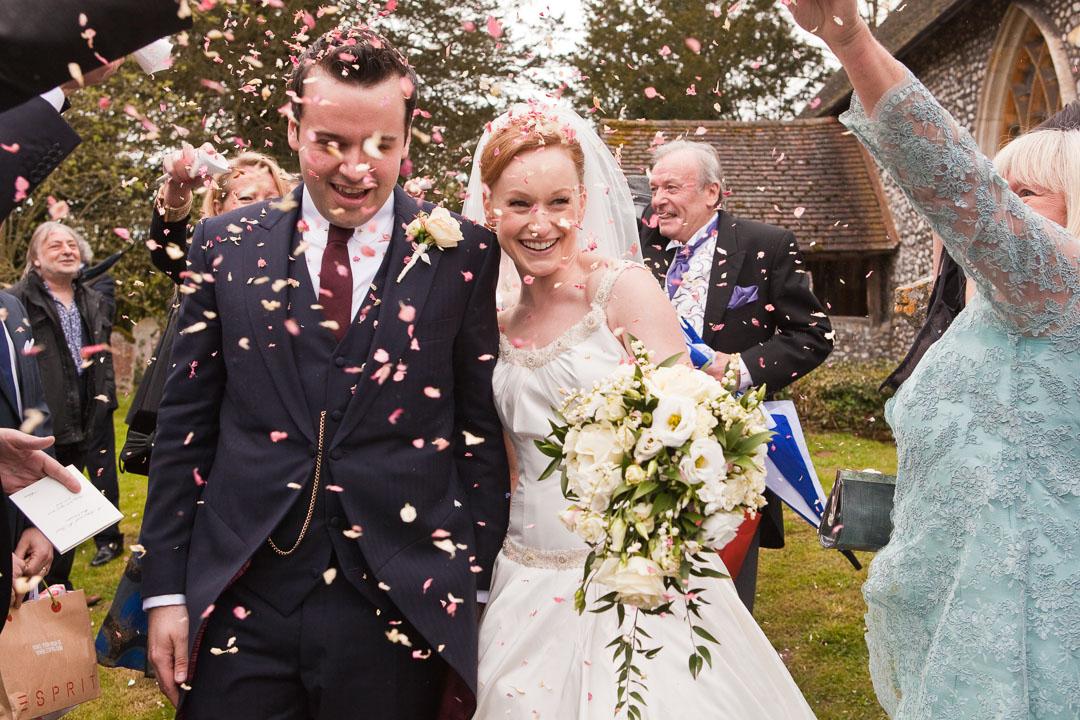 Bride and groom walking through confetti.