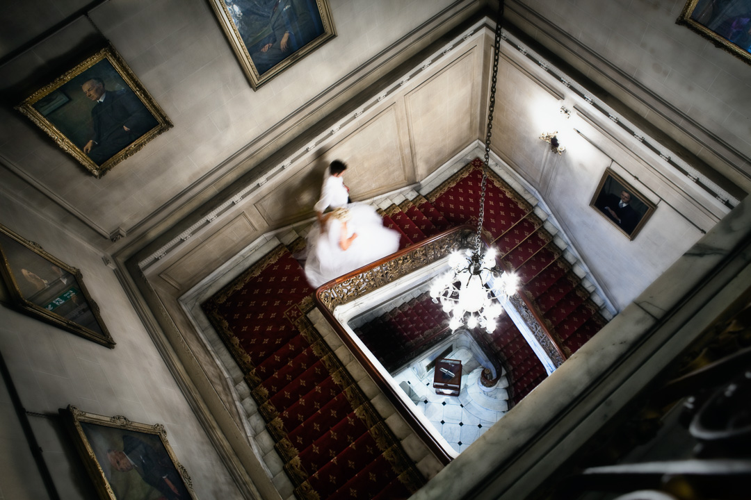 Looking down at the Bride and groom walking down a large lavish staircase.