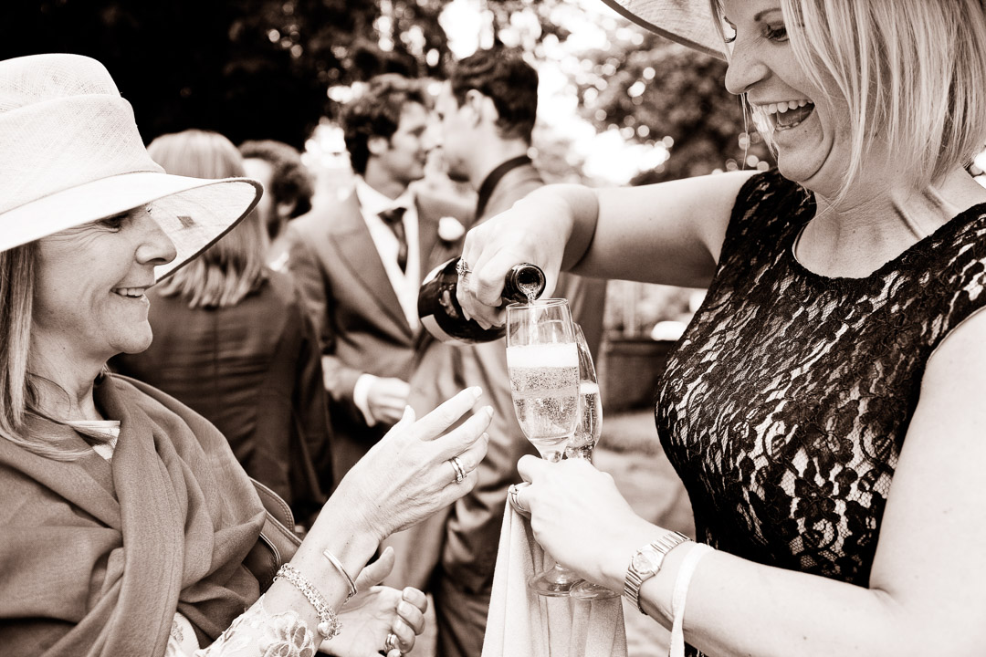 Two ladies pouring Champagne outside the church laughing.