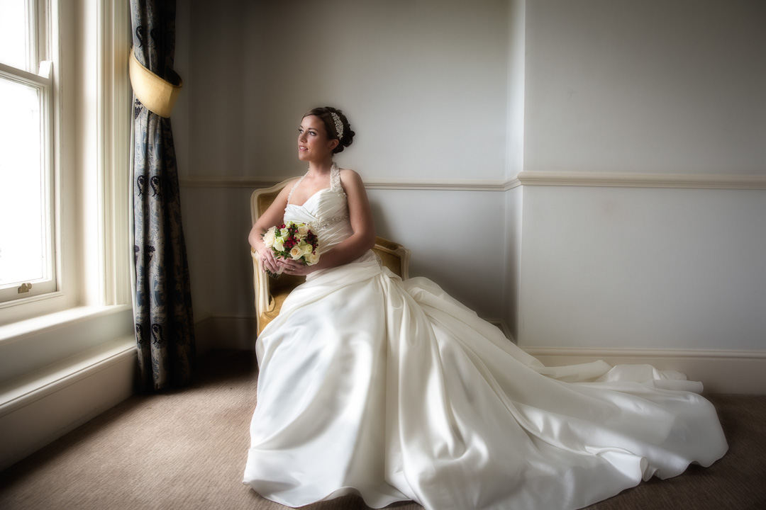 Bride is seated in a chair holding her flowers gazing out of a window.