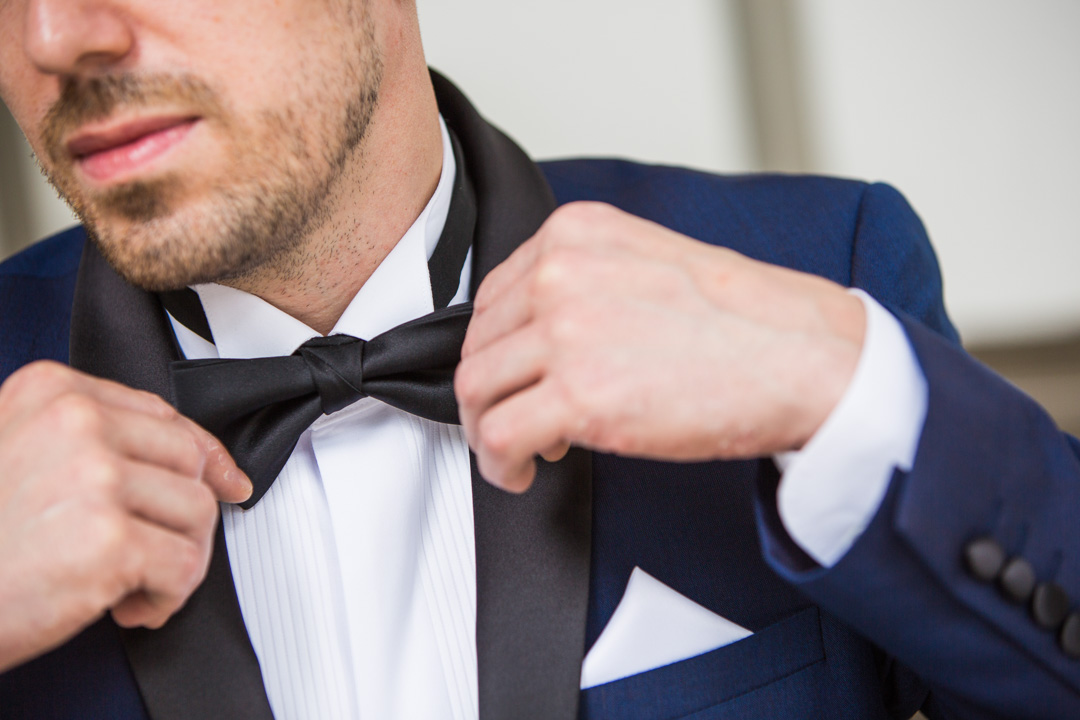 Close crop of groom altering his bowtie.