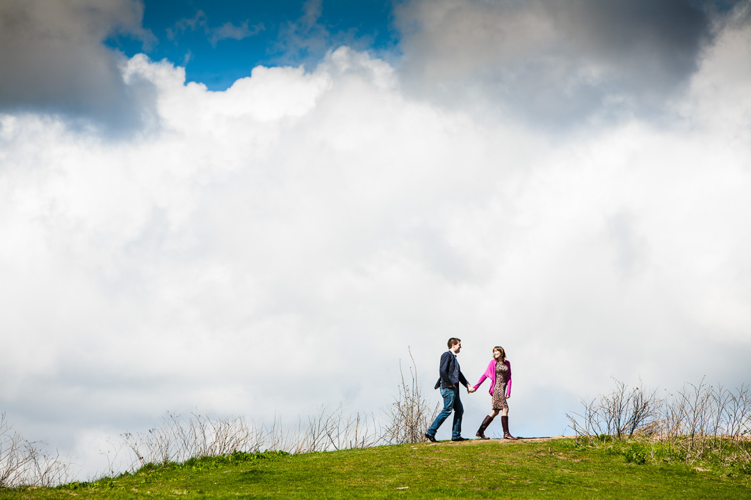 A couple walking on the top of a hill with fluffy clouds behind them.
