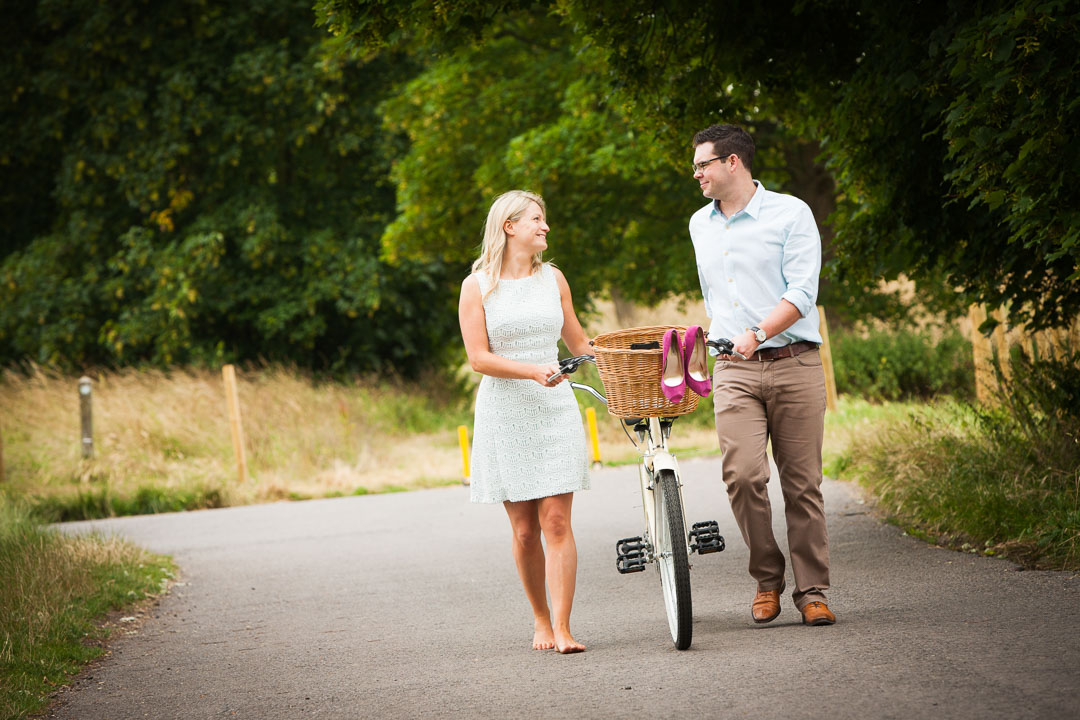 Couple pushing a bicycle in the park looking at each other.