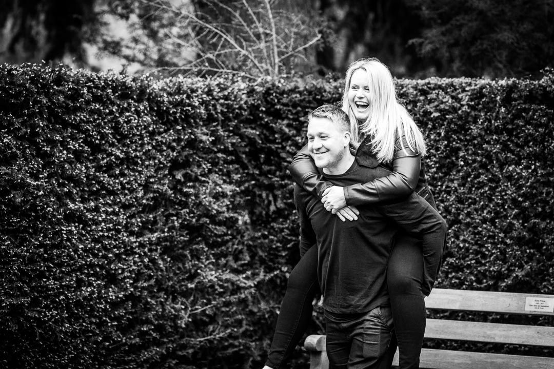 Boyfriend giving his girl a piggyback in front of a hedge.