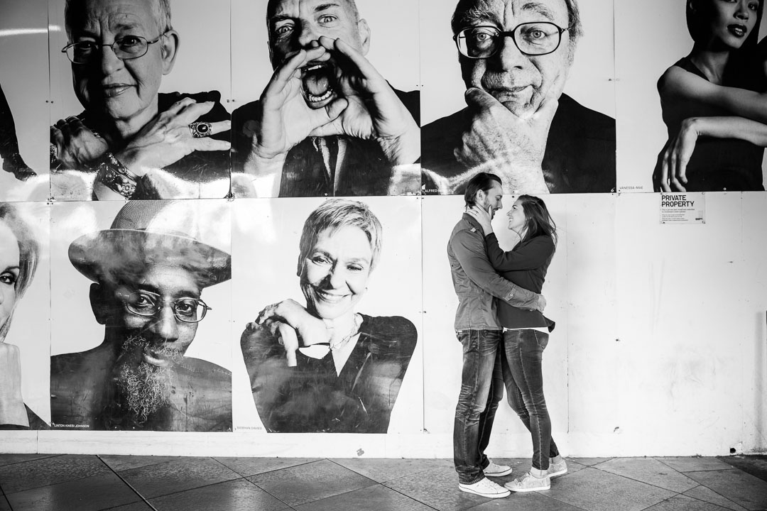 Couple face each other and cuddle in front a poster with six black and white portraits.