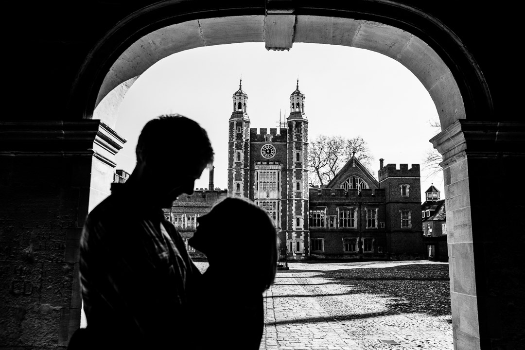 Couple silhouetted under arch in front of school.