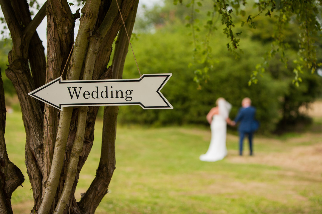 Arrow with wedding written on it hanging on a tree, with the bride and groom in the background walking away.