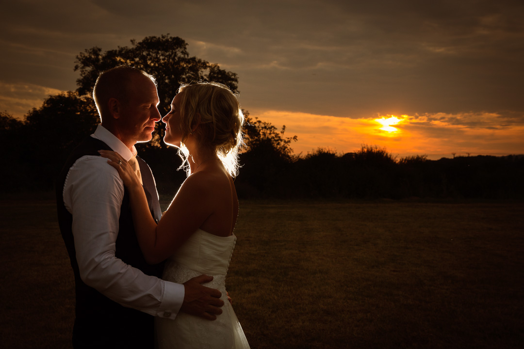 Bride and groom backlit from a sunset