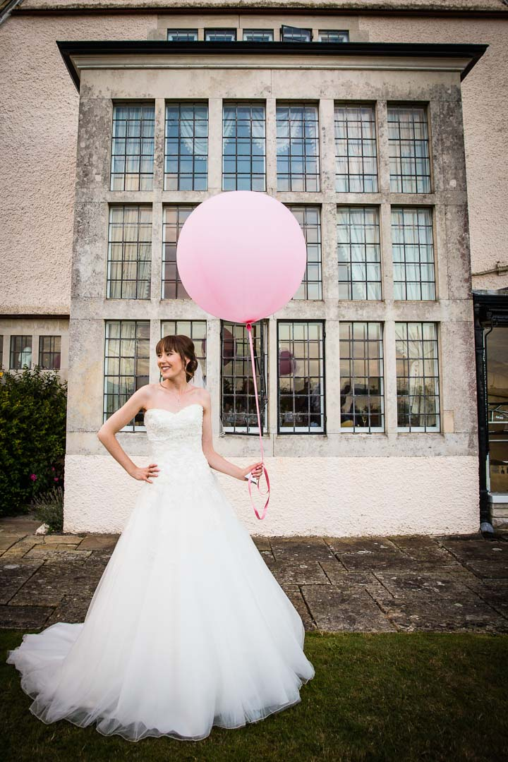 Bride holding pink balloon in front of a window.