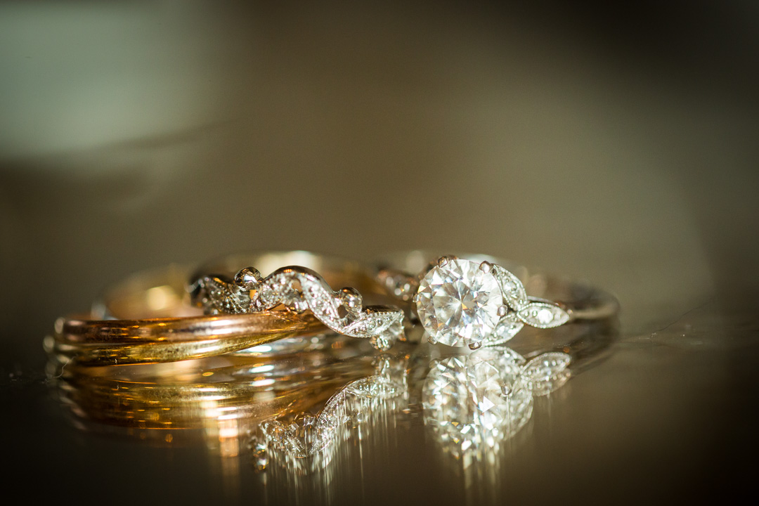 Wedding rings reflecting on glass table.