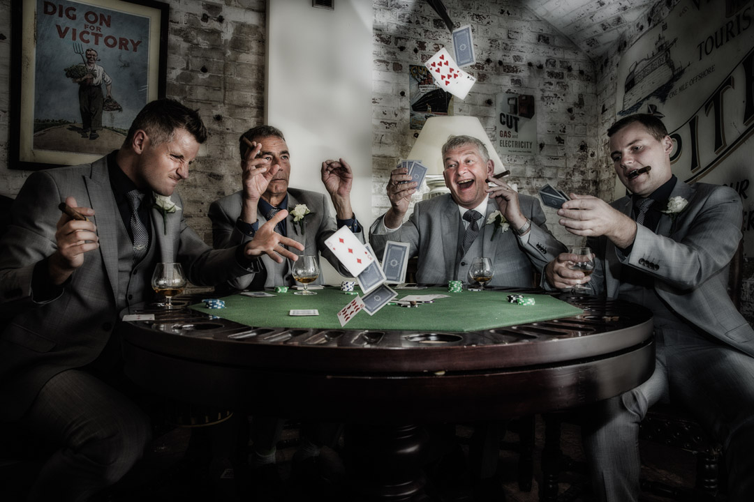Groom and groomsman playing cards, smoking and drinking.
